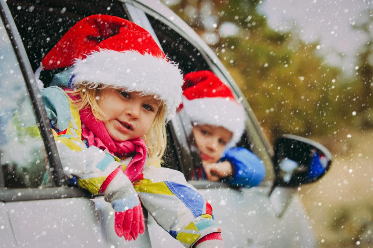 kids wearing santa hats in car
